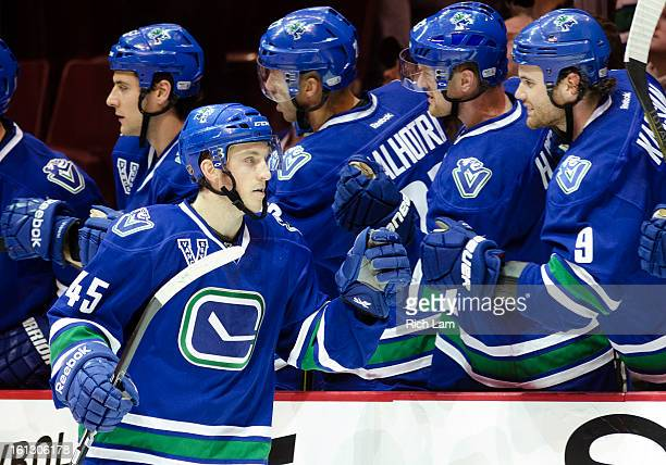 Jordan Schroeder of the Vancouver Canucks is congratulated by Zack Kassian after scoring his second goal of the game and career against the Calgary...