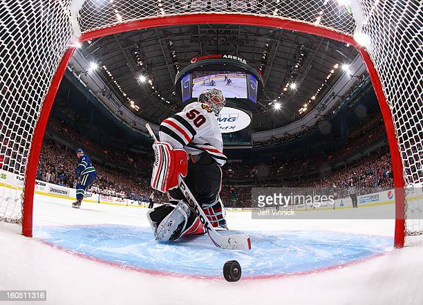 Jordan Schroeder of the Vancouver Canucks looks back as the puck trickles over the line behind Corey Crawford of the Chicago Blackhawks for the...