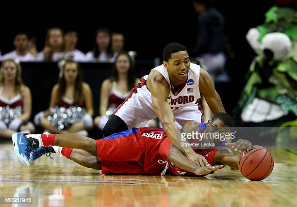 Jordan Sibert of the Dayton Flyers and Anthony Brown of the Stanford Cardinal battle for a loose ball during a regional semifinal of the 2014 NCAA...