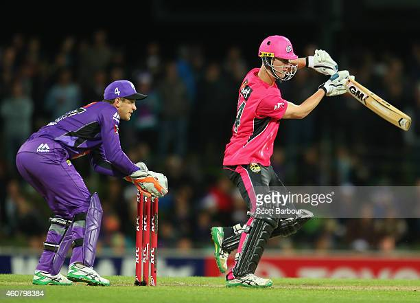 Jordan Silk of the Sixers bats as wicketkeeper Tim Paine of the Hurricanes looks on during the Big Bash League match between the Hobart Hurricanes...