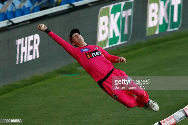 Jordan Silk of the Sixers dives to save a six during the Big Bash League match between the Hobart Hurricanes and Sydney Sixers at Blundstone Arena,...