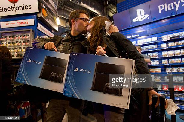 Jordan Smith left and Kayla Brittingham share a kiss after purchasing the Sony PlayStation 4 console during its midnight launch event in San...