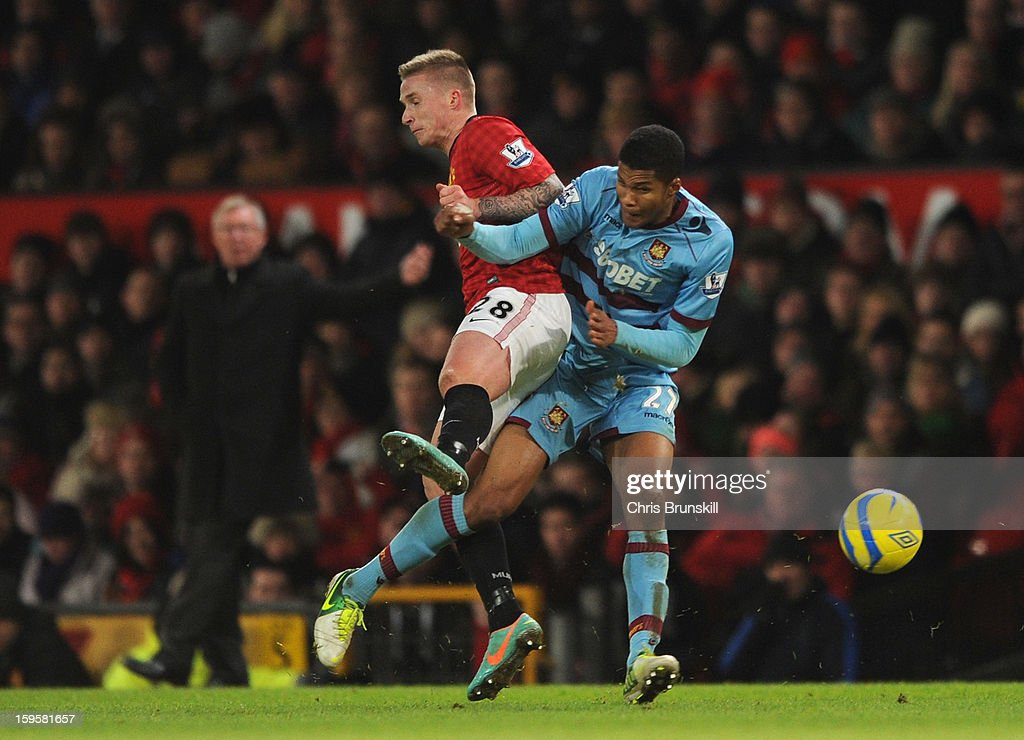 Jordan Spence of West Ham United tangles with Alexander Buttner of Manchester United during the FA Cup with Budweiser Third Round Replay match between Manchester United and West Ham United at Old Trafford on January 16, 2013 in Manchester, England.