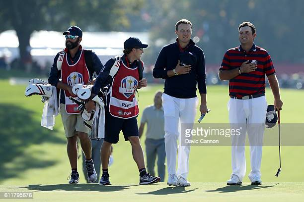 Jordan Spieth and Patrick Reed of the United States walk to the ninth green with their hands on their hearts as the crowd sings the national anthem...