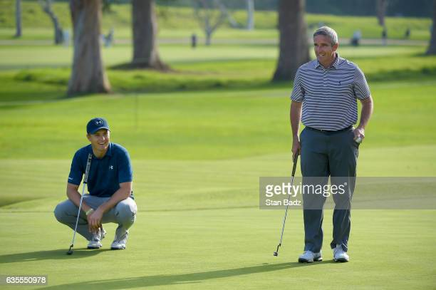 Jordan Spieth and PGA TOUR Commissioner Jay Monahan wait to putt on the 17th hole during the ProAm at the Genesis Open at Riviera Country Club on...