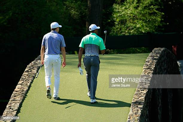 Jordan Spieth and Tiger Woods of the United States walk together over the Hogan Bridge during a practice round prior to the start of the 2015 Masters...