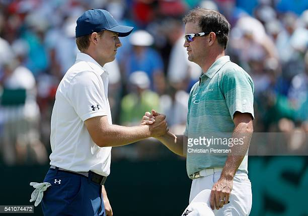 Jordan Spieth and Zach Johnson of the United States shake hands following the completion of the continuation second round of the US Open at Oakmont...