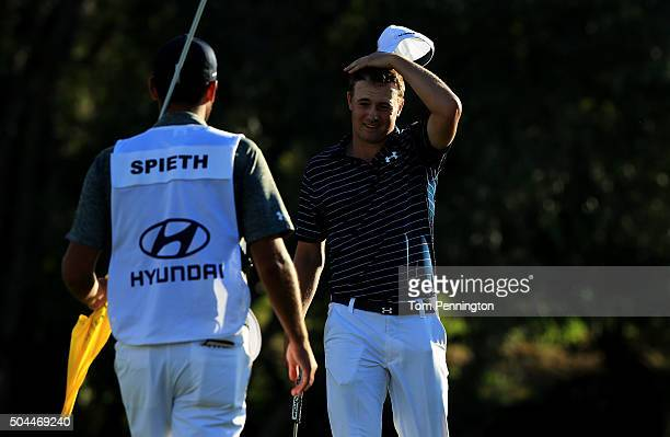 Jordan Spieth celebrates with caddie Michael Greller on the 18th green after putting for birdie to go 30 under and win the final round of the Hyundai...