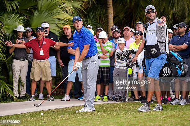 Jordan Spieth checks his approach from the 10th hole rough with caddie Michael Greller as fans watch during the second round of the World Golf...