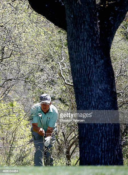 Jordan Spieth checks his line out of the rough on the fourth hole during the final round of the Valero Texas Open at TPC San Antonio ATT Oaks Course...