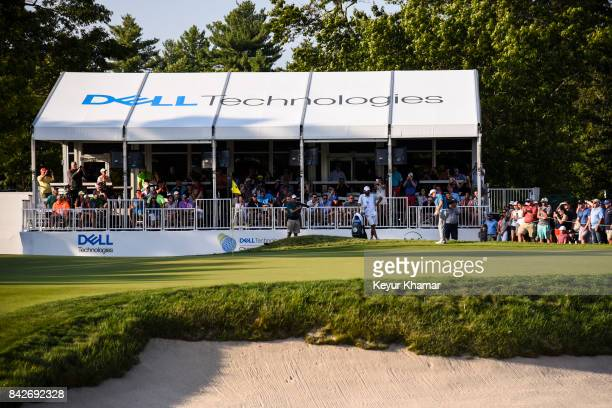 Jordan Spieth chips a shot to the 15th hole green in front of a hospitality tent during the final round of the Dell Technologies Championship at TPC...