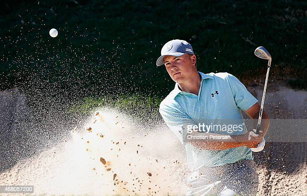 Jordan Spieth chips from the bunker onto the 18th green during the final round of the Valero Texas Open at TPC San Antonio ATT Oaks Course on March...