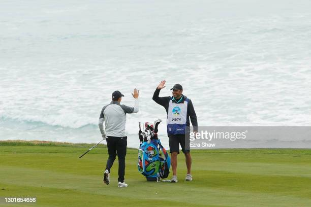 Jordan Spieth of the United States and caddie Michael Greller celebrate his eagle on the tenth hole during the first round of the AT&T Pebble Beach...