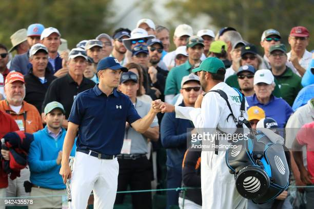 Jordan Spieth of the United States and caddie Michael Greller fist-bump on the 18th hole during the first round of the 2018 Masters Tournament at...