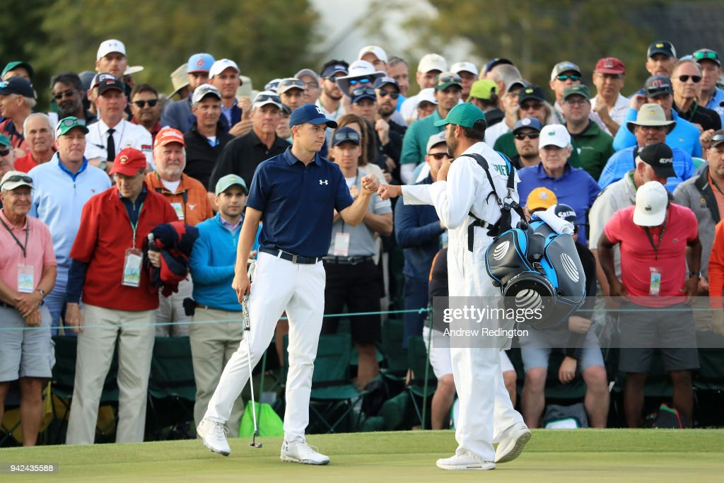 Jordan Spieth of the United States and caddie Michael Greller fist-bump on the 18th hole during the first round of the 2018 Masters Tournament at Augusta National Golf Club on April 5, 2018 in Augusta, Georgia.