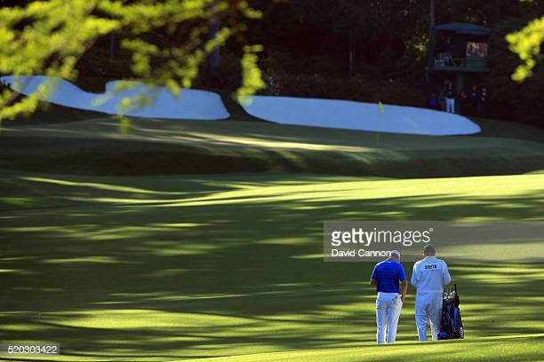 Jordan Spieth of the United States and caddie Michael Greller prepare to play a shot on the 13th hole during the final round of the 2016 Masters...
