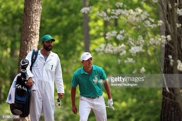Jordan Spieth of the United States and caddie Michael Greller react to his second shot on the 11th hole during the first round of the 2016 Masters...