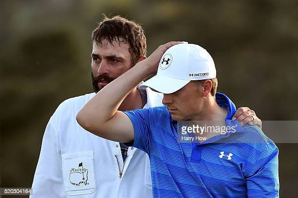Jordan Spieth of the United States and caddie Michael Greller react after finishing on the 18th green during the final round of the 2016 Masters...