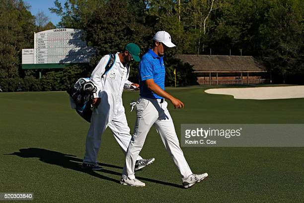 Jordan Spieth of the United States and caddie Michael Greller walk from the 12th tee during the final round of the 2016 Masters Tournament at Augusta...
