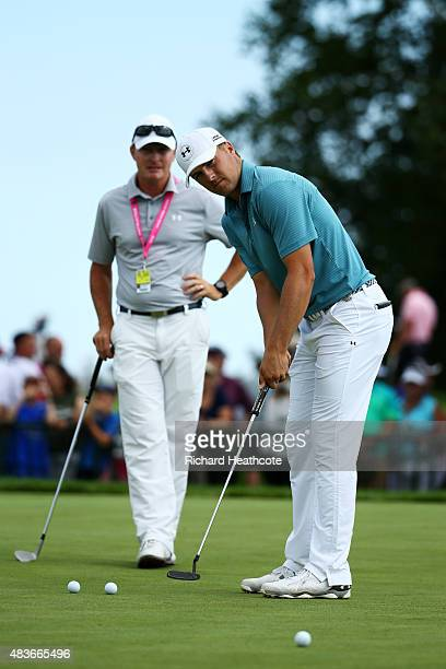 Jordan Spieth of the United States and his coach Cameron McCormick practice on the putting green during a practice round prior to the 2015 PGA...