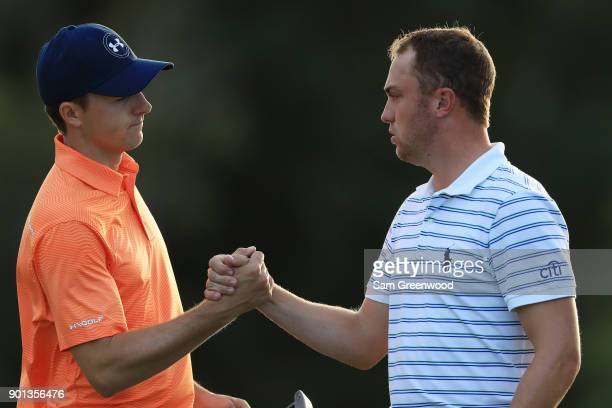 Jordan Spieth of the United States and Justin Thomas of the United States shake hands on the 18th green after finishing the first round of the Sentry...