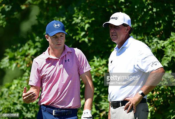 Jordan Spieth of the United States and Phil Mickelson of the United States talk as they wait on a tee during a practice round prior to the 2016 PGA...