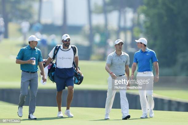 Jordan Spieth of the United States caddie Michael Greller Rory McIlroy of Northern Ireland and Justin Thomas of the United States walk on the tenth...