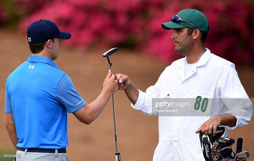 Jordan Spieth of the United States celebrates his birdie on the par four 10th hole with his caddie during the first round of the 2015 Masters at Augusta National Golf Club on April 9, 2015 in Augusta, Georgia.
