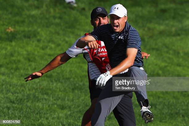 Jordan Spieth of the United States celebrates with caddie Michael Greller after chipping in for birdie from a bunker on the 18th green to win the...