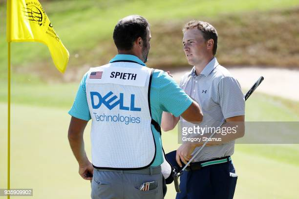 Jordan Spieth of the United States celebrates with caddie Michael Greller after defeating Charl Schwartzel of South Africa 31 on the 17th green...