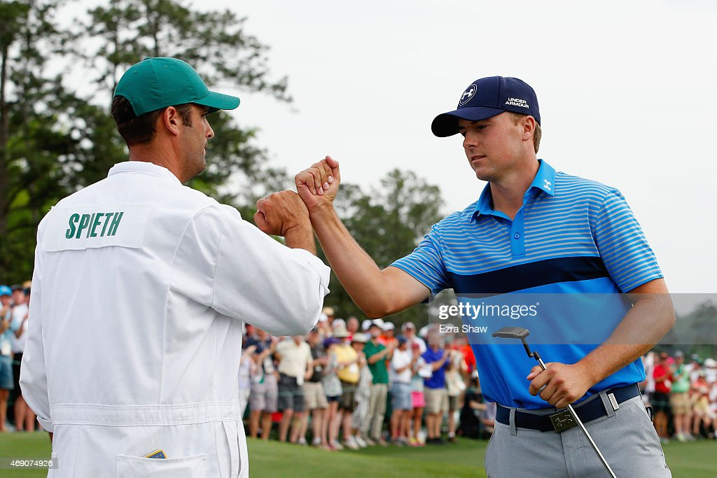 Jordan Spieth of the United States celebrates with his caddie Michael Greller on the 18th green after an eighth-under par 64 during the first round of the 2015 Masters Tournament at Augusta National Golf Club on April 9, 2015 in Augusta, Georgia.