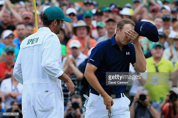 Jordan Spieth of the United States celebrates with his caddie Michael Greller on the 18th green after his four-stroke victory at the 2015 Masters...