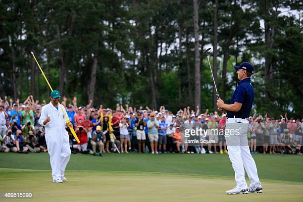 Jordan Spieth of the United States celebrates with his caddie Michael Greller on the 18th green after his fourstroke victory at the 2015 Masters...