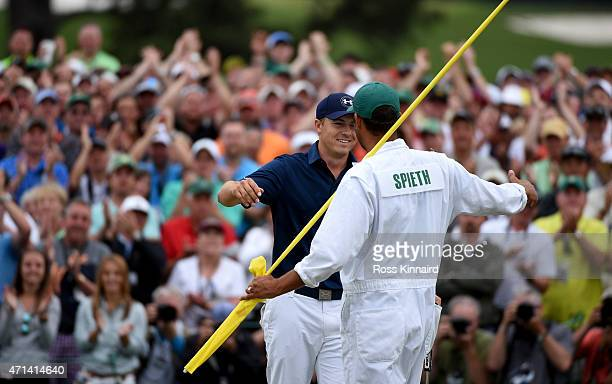 Jordan Spieth of the United States celebrates with his caddie Michael Greller after the final round of the 2015 Masters at Augusta National Golf Club...