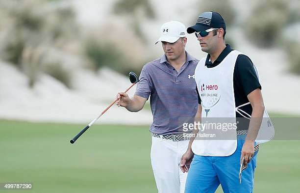 Jordan Spieth of the United States chats with his caddie Michael Greller on the third hole during the first round of the Hero World Challenge at...
