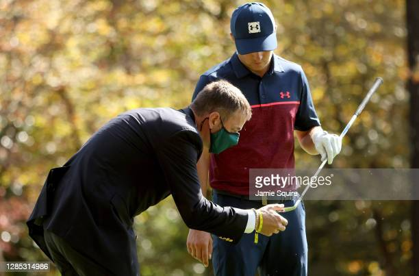 Jordan Spieth of the United States checks his club with a rules official before playing a shot on the 11th hole during the first round of the Masters...