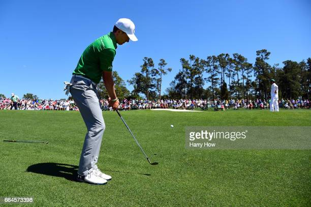 Jordan Spieth of the United States chips on the 18th green during a practice round prior to the start of the 2017 Masters Tournament at Augusta...