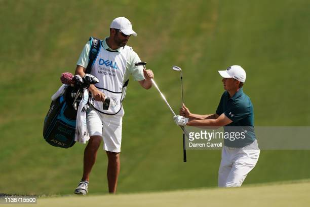 Jordan Spieth of the United States exchanges clubs with caddie Michael Greller in his match against Billy Horschel of the United States during the...