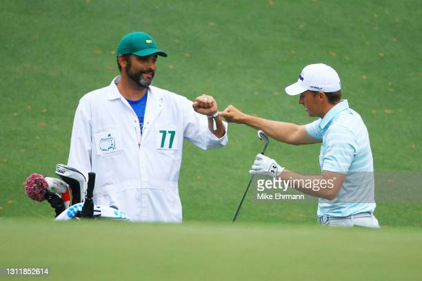 Jordan Spieth of the United States fist bumps his caddie, Michael Greller, after chipping in for birdie on the tenth hole during the third round of...