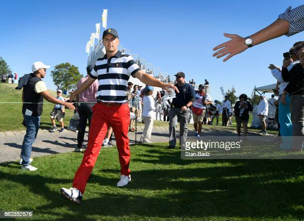 Jordan Spieth of the United States greets fans along the second hole during the Sunday singles matches at the Presidents Cup at Liberty National Golf...