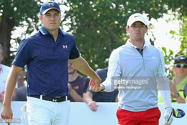 Jordan Spieth of the United States hands back a teepeg to Rory McIlroy of Northern Ireland on the 17th hole during the continuation of the second...