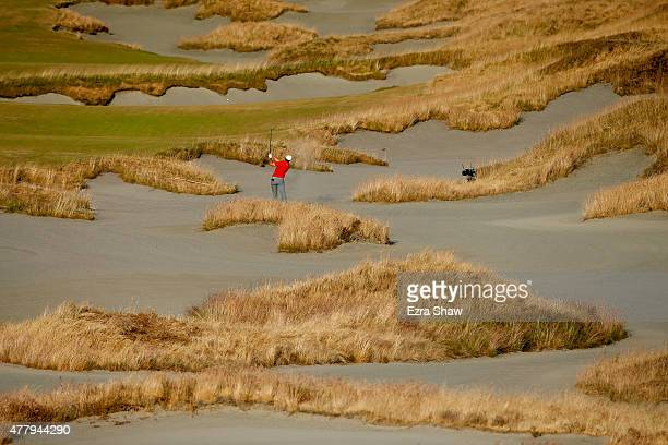 Jordan Spieth of the United States hits a shot from a bunker on the 18th hole during the third round of the 115th U.S. Open Championship at Chambers...