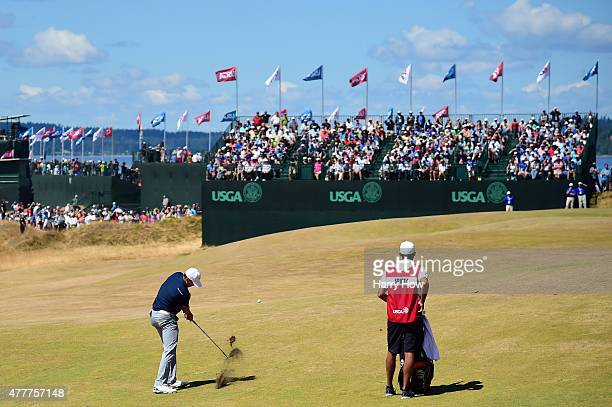 Jordan Spieth of the United States hits his third shot on the first hole as caddie Michael Greller looks on during the second round of the 115th U.S....