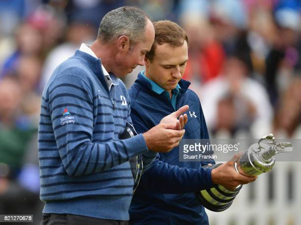 Jordan Spieth of the United States holds the Claret Jug as he is congratulated by Matt Kuchar of the United States on the 18th green during the final...