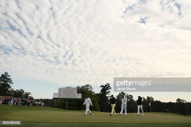 Jordan Spieth of the United States Justin Thomas of the United States caddie Michael Greller and caddie James Johnson walk off the 18th green during...