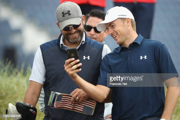 Jordan Spieth of the United States laughs whilst looking at his phone with his caddie Michael Greller during previews to the 147th Open Championship...