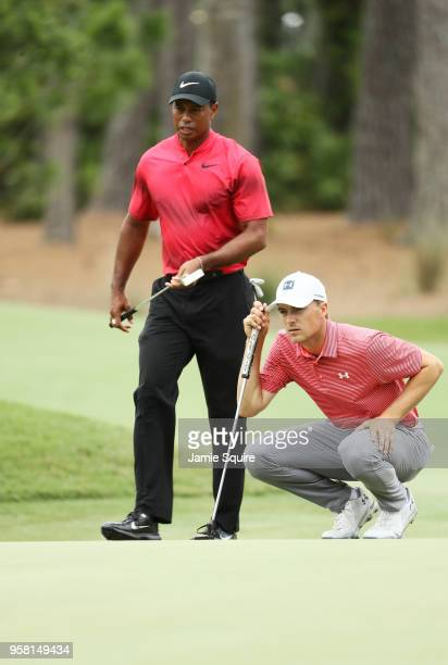 Jordan Spieth of the United States lines up a putt on the first green as Tiger Woods of the United States looks on during the final round of THE...