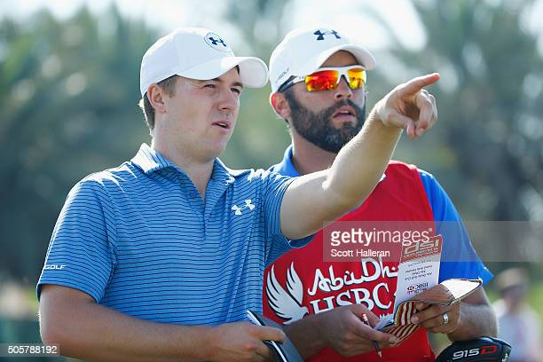 Jordan Spieth of the United States lines up a shot with his caddie Michael Greller during the pro-am as a preview for the 2016 Abu Dhabi HSBC Golf...