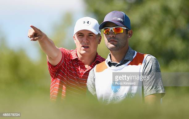 Jordan Spieth of the United States lines up his tee shot on the seventh hole with his caddie Michael Greller during the second round of The Barclays...