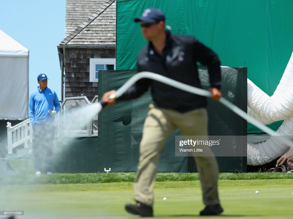 Jordan Spieth of the United States looks on as a member of the grounds crew waters a green during practice rounds prior to the 2018 U.S. Open at Shinnecock Hills Golf Club on June 11, 2018 in Southampton, New York.